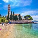 Hvar, Croatia, August 25, 2014: Hvar island turquoise beach and stone church in Dalmatia, Croatia. Hvar church is famous ancient monument visited by many tourist.